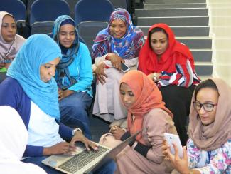 women researchers gathered around a laptop